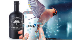 Whiskey bottle with mobile phone and hummingbird
