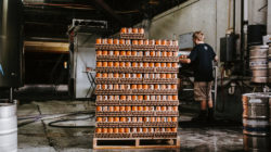 Pallet of beer cans in warehouse with man